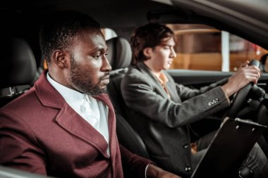 Driving teacher. African-American driving teacher assisting his young client sitting behind the wheel