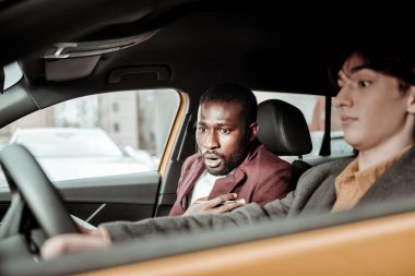 Bearded driving instructor feeling worried while student parking car