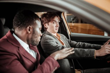 Young dark-eyed man feeling scarred while learning driving