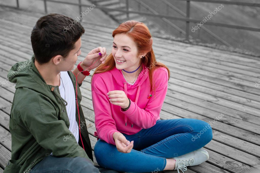 Kind young man giving his girlfriend earphones and sharing music