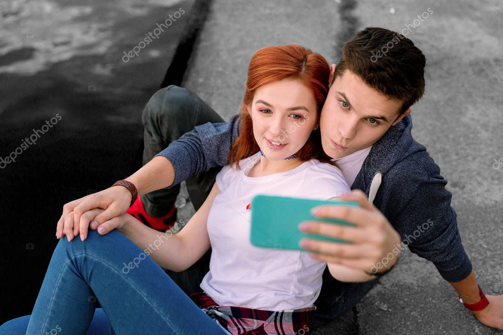 Dark-haired stylish teen girl holding her smartphone while making selfie with friend