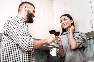 Just married man and woman clanging their glasses with wine