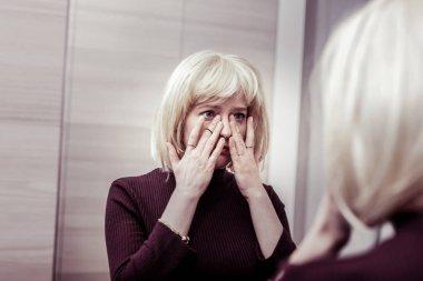 Worried blonde girl wiping tears from eyes