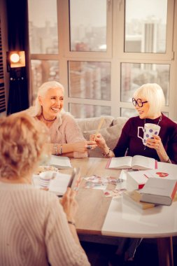 Delighted cheerful aged woman taking a cookie
