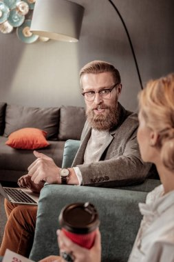 Delighted bearded male person looking at his interlocutor