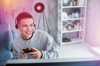 Handsome student feeling joyful holding joystick playing video games