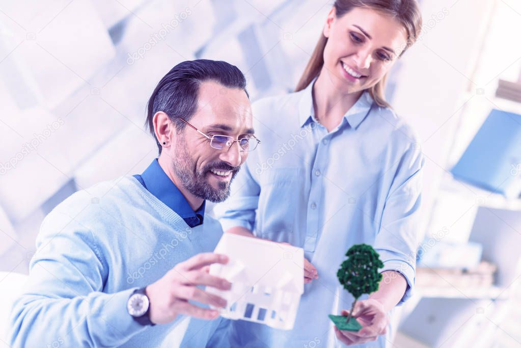 Cheerful engineers working with trees and houses miniatures and smiling