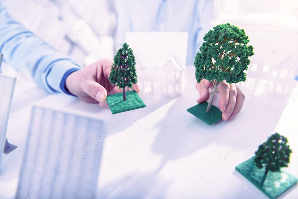 Two architects placing miniature trees while working on new project