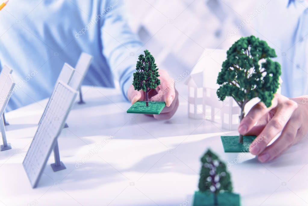 Two people holding miniature trees while working on their project