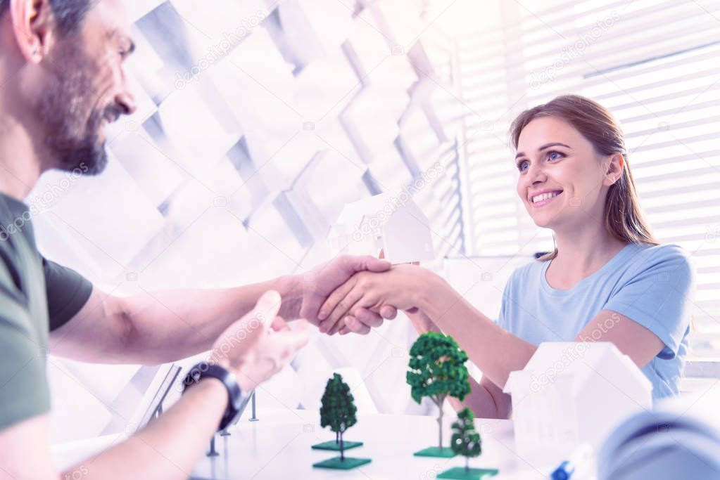Cheerful woman shaking hands with friendly man and smiling