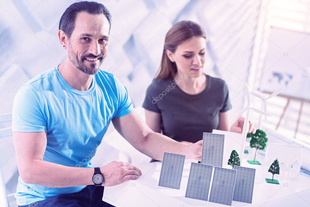Positive architect sitting at the table and working with solar batteries
