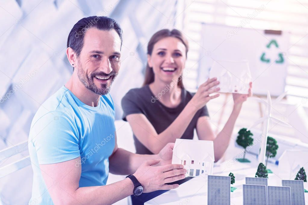 Emotional eco engineers smiling and showing their futuristic eco houses