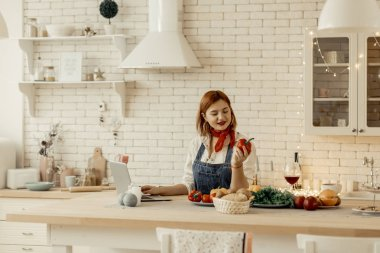 Beautiful young red-haired girl with big earrings holding a red pepper in her hand
