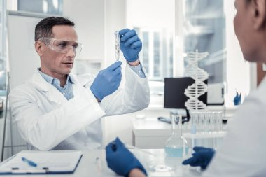 Concentrated biologist looking on the content of the test tube
