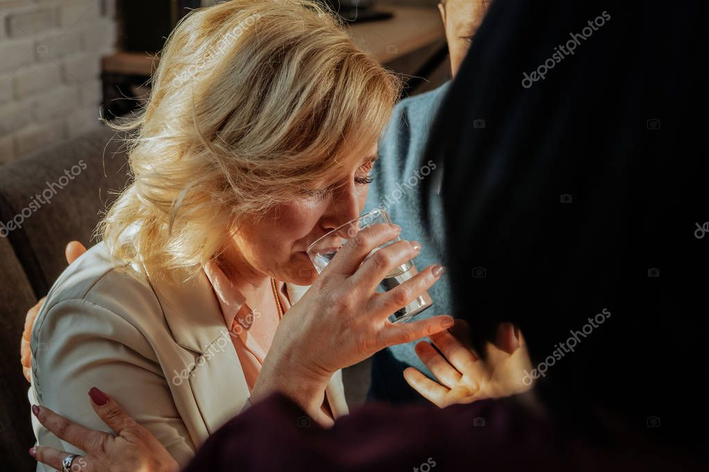 Effective short-haired woman sipping water from wide glass