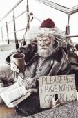 nachdenklicher alter Almosenempfänger sitzt und liest Buch, während er versucht, sich ein paar Almosen zu verdienen.