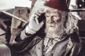 alter Almosenempfänger findet neues Telefon und beschließt, jemanden anzurufen.