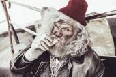 obdachlose ältere Menschen essen Brötchen, die er für Almosen kauft und schauen in die Kamera.