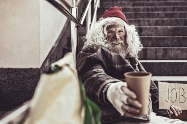 Homeless elderly offering his cap whose he holding in one hand for alms.