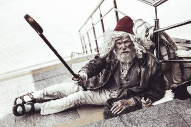 Caucasian beggar giving fallen cane to man passing by.