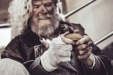 Caucasian homeless man happy to get a bun and holding it with both hands.