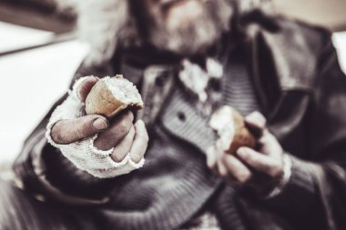 Close up photo of the homeless man holding two pieces of baking with both hands.