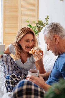 Husband and wife enjoying yummy croissants and coffee in bed