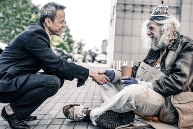 Curious short-haired businessman sitting in front of long-haired homeless