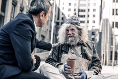 Smiling happy long-haired homeless man taking money from kind businessman