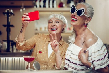 Happy aged women posing for selfie together