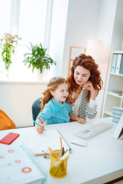 Cheerful girl painting while joining mother working on computer