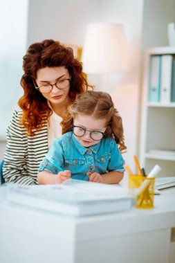 Businesswoman watching her funny daughter in glasses painting