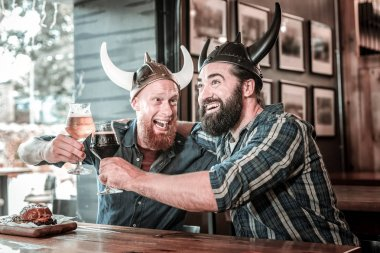 Two friends wearing viking helmets and laughing.