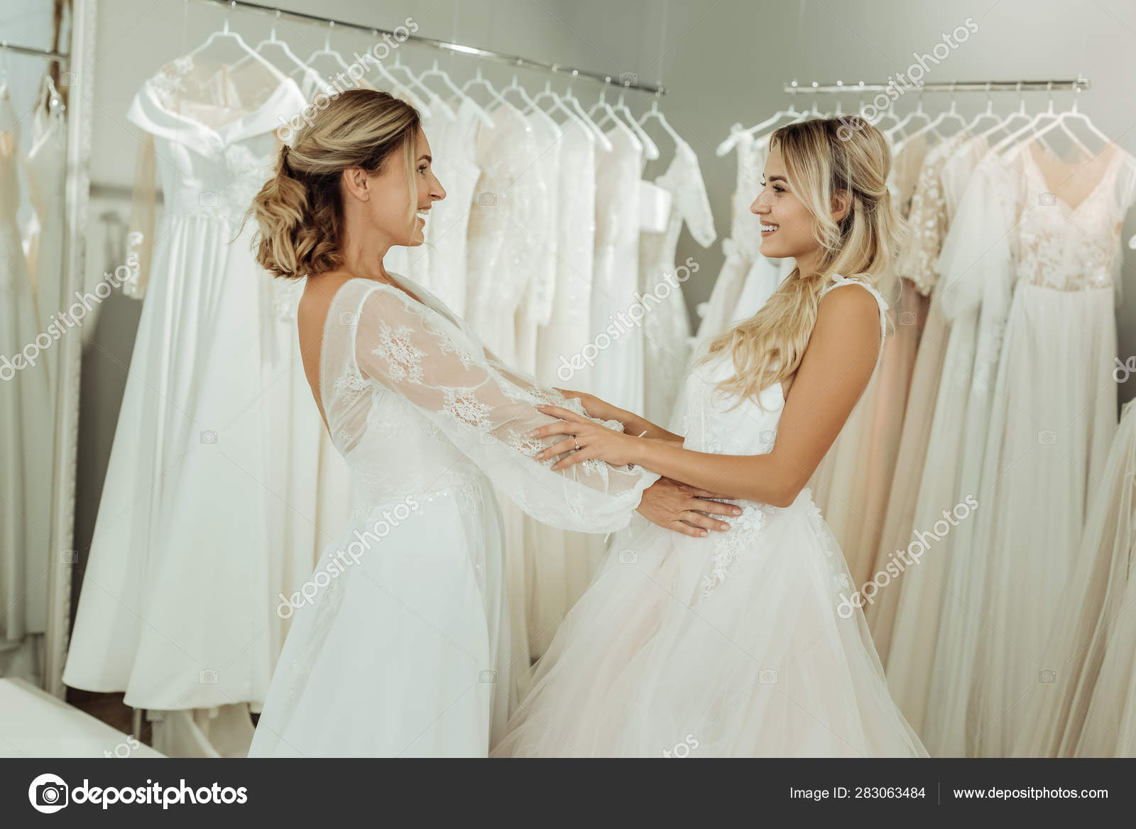 Two Friends Trying On Wedding Dresses Together Stock