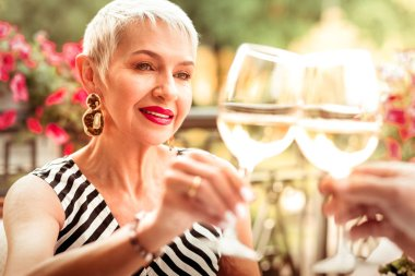 Mature woman wearing massive earrings drinking wine with husband