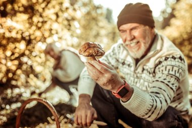 Big mushroom in a hand of happy man.