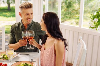 Handsome man looking at his beautiful wife while drinking wine
