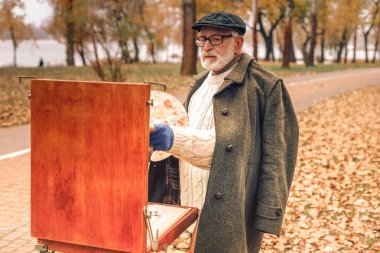 Elderly man painting in the autumnal park