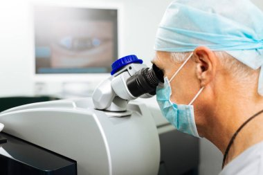 Professional serious doctor using the microscope for work