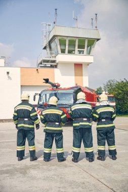 Dört güçlü adam ateşin önünde modern kamyonun önünde duruyor.