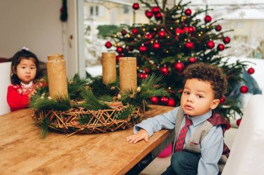 Adorable 3 year old toddler kids enjoying Christmas time, playing with candles