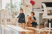 Két vicces gyerekek játszottak együtt teddy bear otthon töltött-val napfény fehér nappali