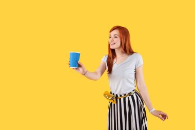 Delighted optimistic woman standing against yellow background