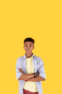 Pleasant thoughtful man standing against yellow background