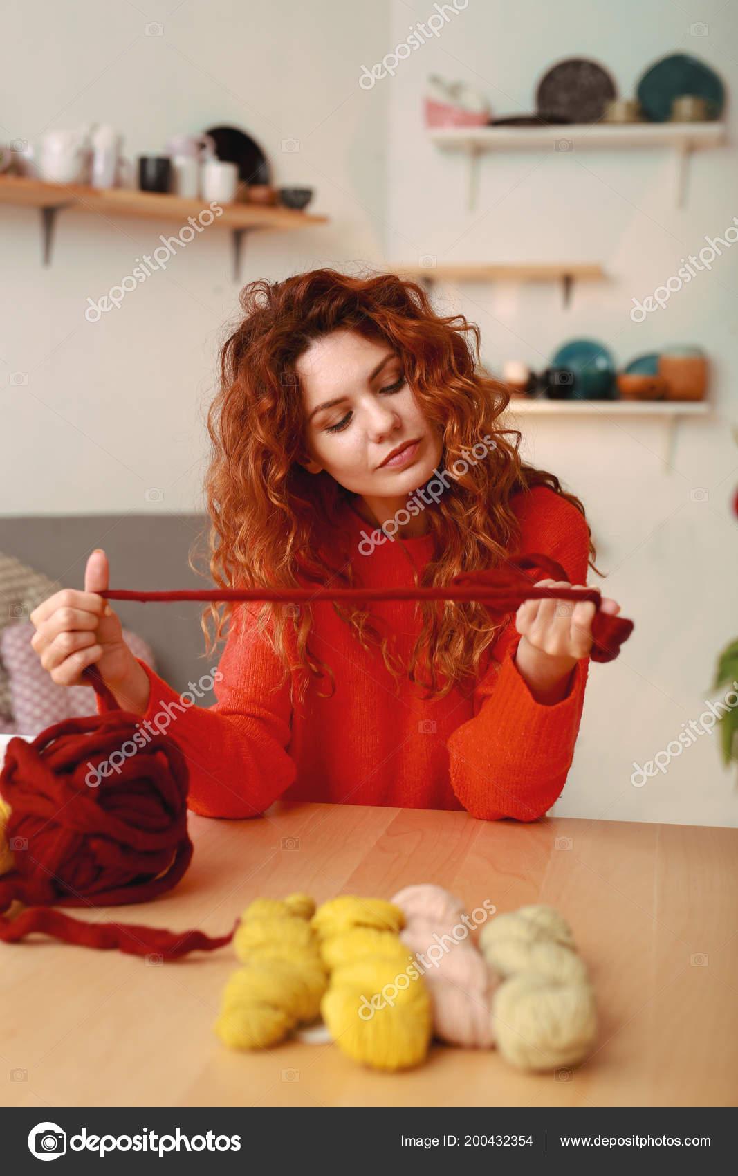 Háčkované podprocesu. Atraktivní raního dívka nosí zářivě červený svetr  drží husté kaštanové háčkování vlákno — Fotografie od ... 6e489effe2