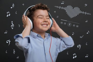 Positive child closing his eyes while listening to music