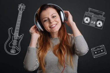 Cheerful woman smiling and listening to music in her headphones