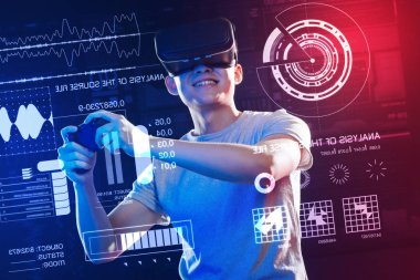 Excited man holding a game console while wearing virtual reality glasses