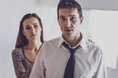 Depressed nice man standing in front of his wife