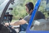 Fényképek Pontos adatokat. Sportos fiatal férfi ellenőrzése a paraméterek egy helikopter, az irányítópulton felkészülése a repülés